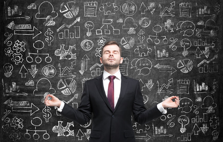 Meditative businessman is looking for the best solution for the business development process. Business icons are drawn over the huge blackboard.